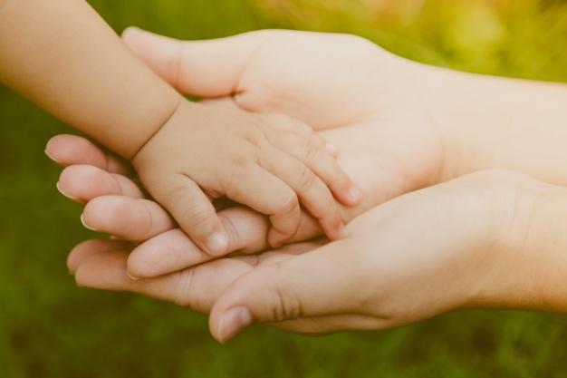mano-de-adulto-agarrando-mano-de-un-bebe_1232-1377